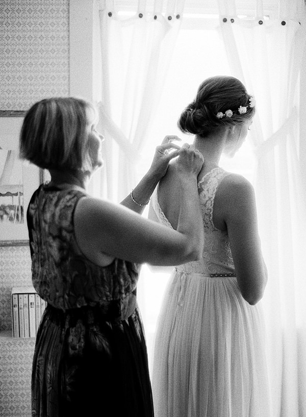 bride's mom helping put dress on