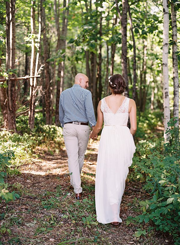 bride and groom walking into the woods