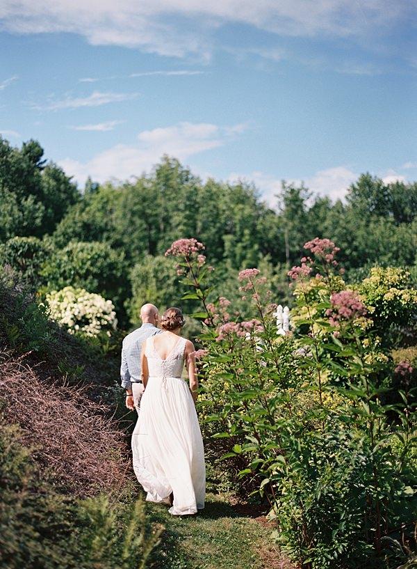 bride and groom walking through garden