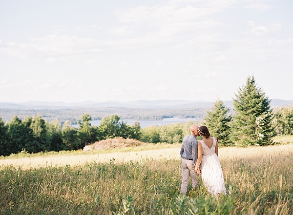 bride and groom kissing in mountains