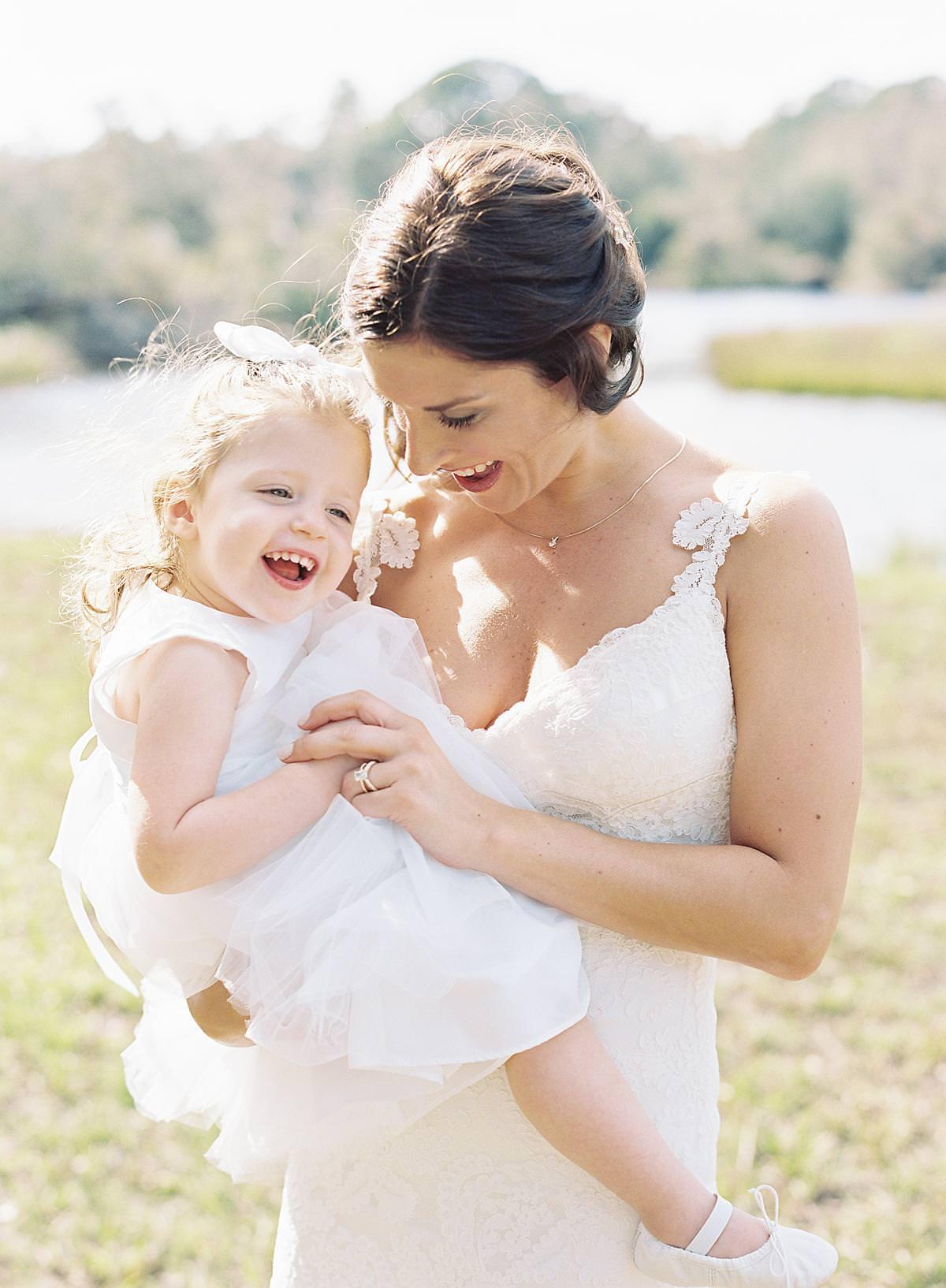 bride holding flower girl