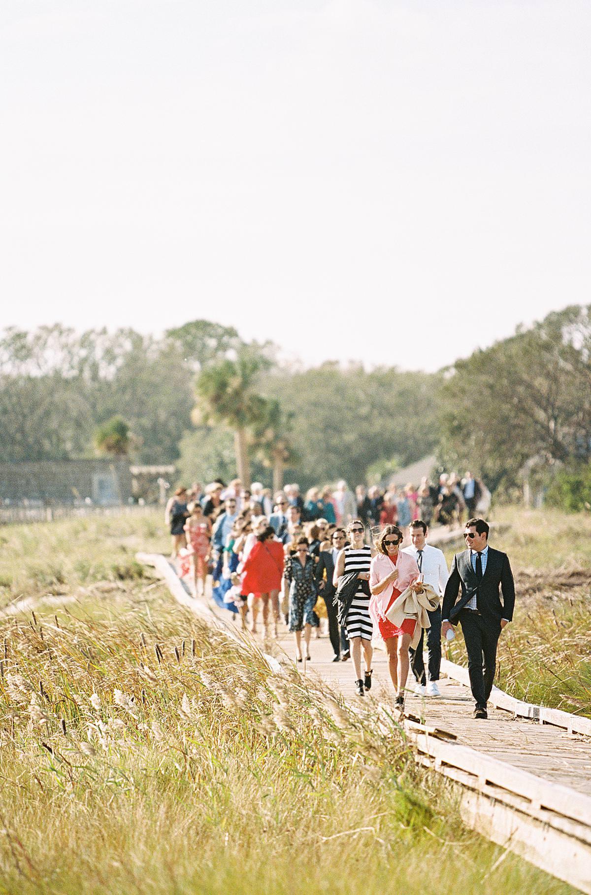 wedding guests on beach boardwalk
