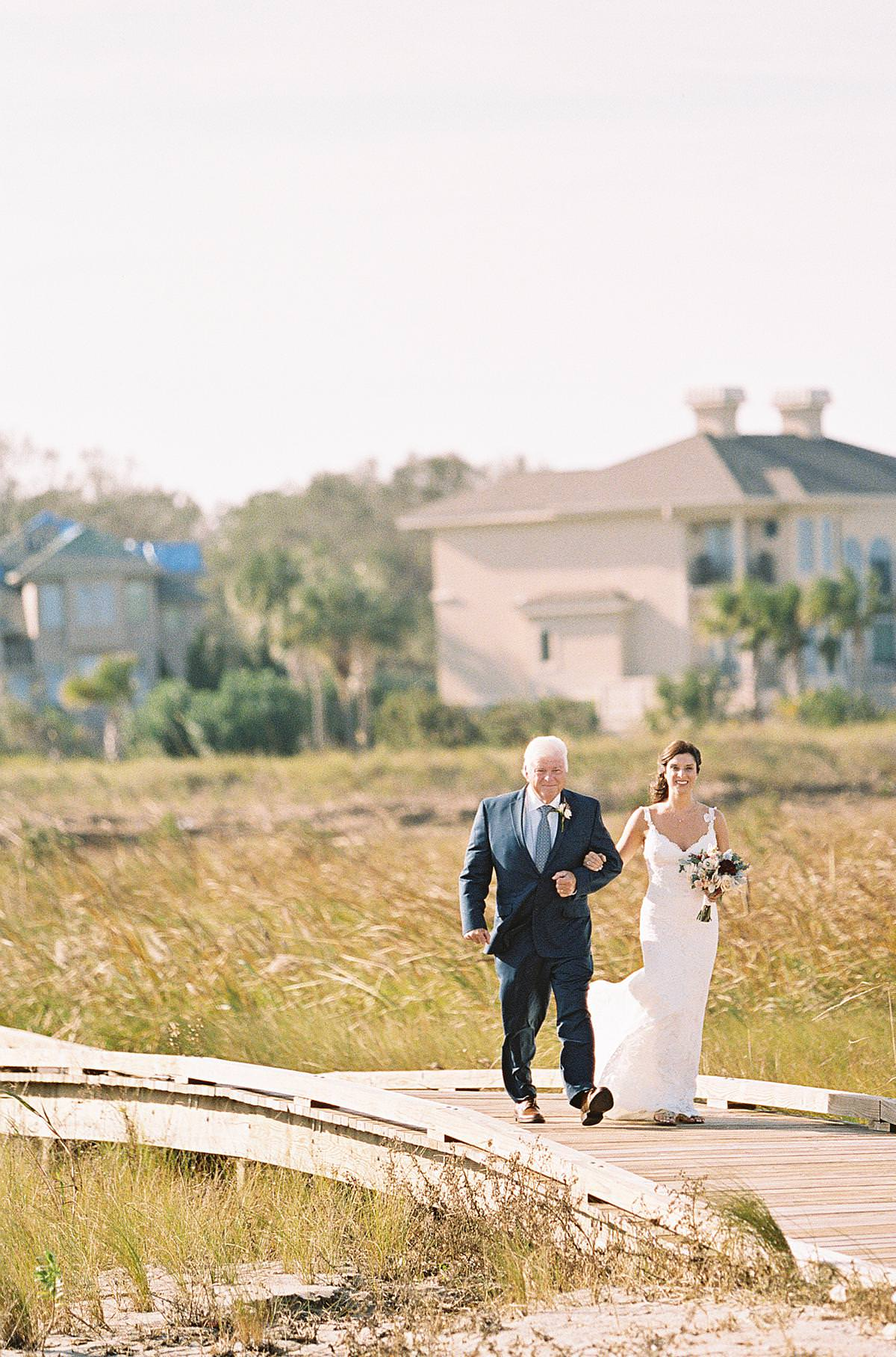 father walking bridal to beach ceremony