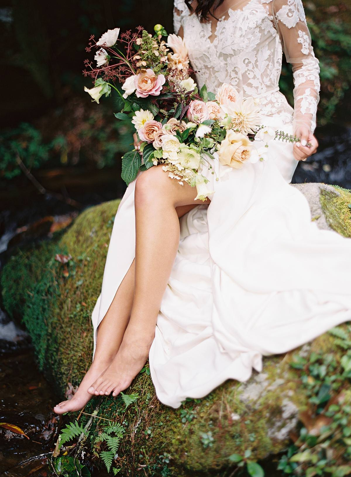 bride sitting beside stream