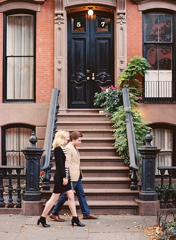 couple walking near brownstones