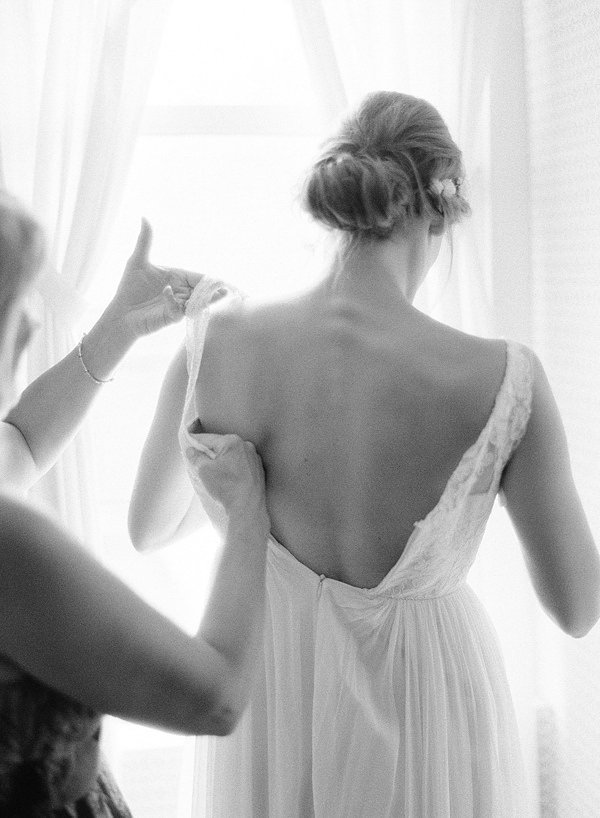 bride getting dressed on black and white film