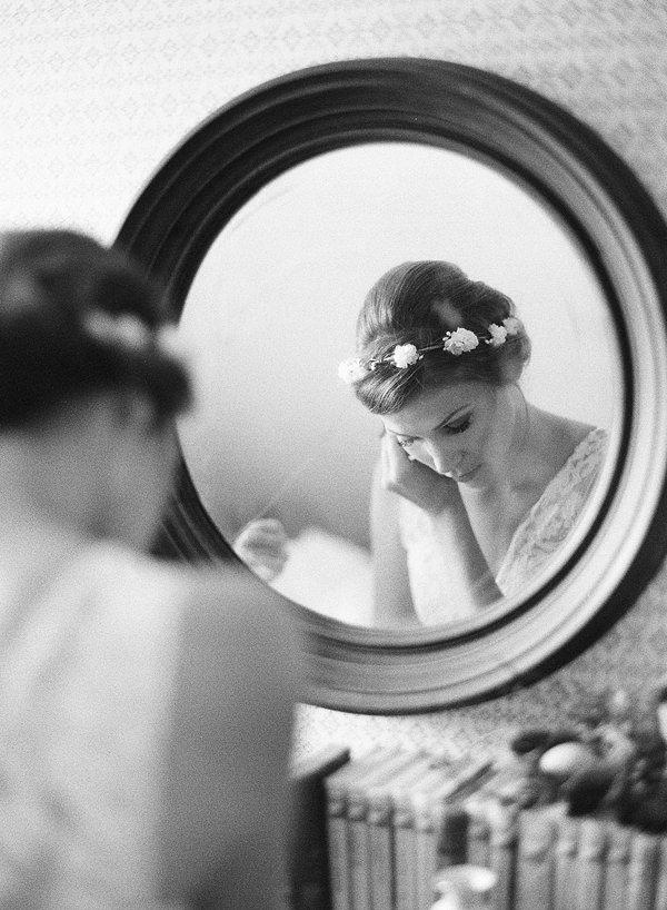 bride putting earrings on in mirror