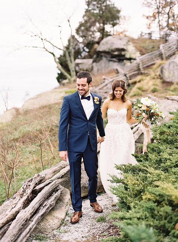 bride and groom walking cliffside