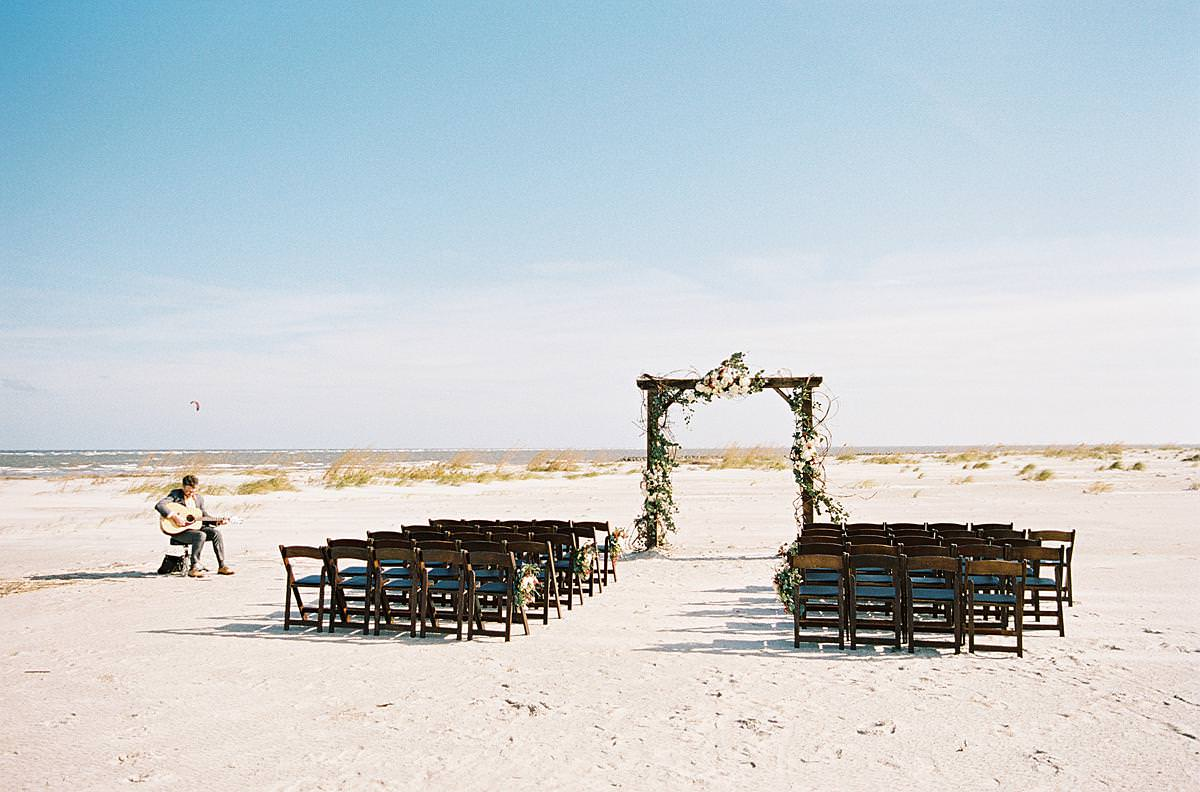 beach ceremony with dark wooden chairs